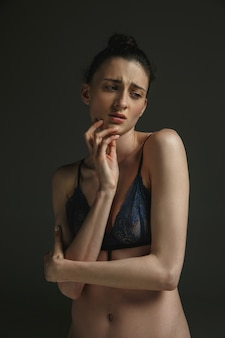 Half-length portrait of young sad woman in underwear on dark wall. sadness, depression and addiction. concept of human emotions, feminism, woman's problems and rights, mental health.
