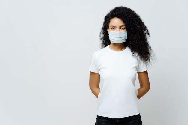 Half length shot of afro american woman being on self isolation or quarantine, wears medical mask during coronavirus outbreak