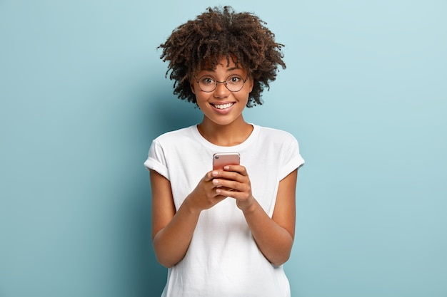 Mezza lunghezza colpo di donna afro tiene il cellulare, gode di belle chiacchiere online nei social network, legge articoli divertenti su internet