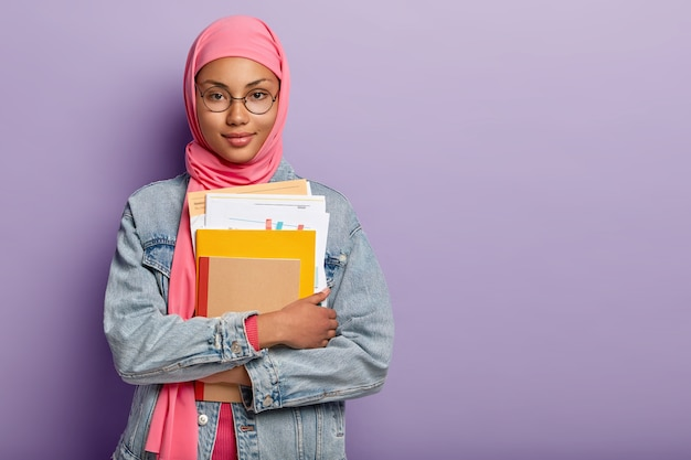 Half length shot of attractive confident muslim college student holds notebooks, paper documents, prepares project work on lesson, wears pink hijab, round spectacles, jean clothes. studying concept
