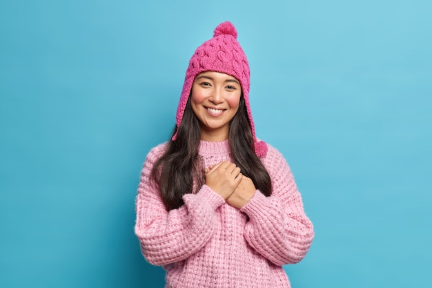 Half length shot of beautiful asian woman in knitwear being thankful for heartwarming words smiles pleasantly poses against blue wall