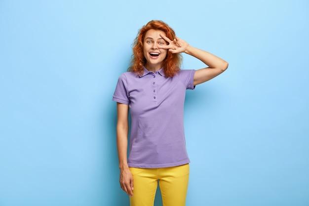 Il colpo a mezzo busto di una bella ragazza dai capelli rossi mostra il gesto di vittoria della pace, si sente ottimista e fortunato