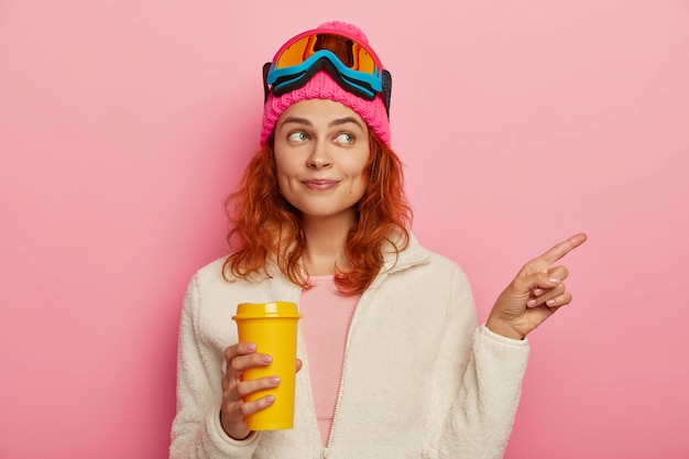Half length shot of beautiful redhead girl points right, shows direction to tourist in resort place, has active winter rest, drinks takeaway coffee, wears ski mask, isolated over pink background