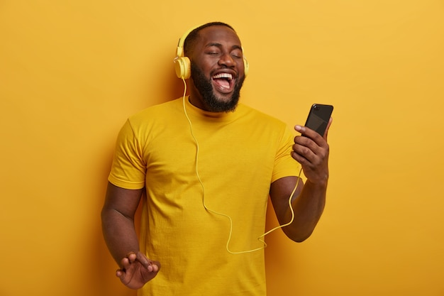 Half length shot of black guy listens music to chill, holds modern smartphone and wears headphones on ears, enjoys nice track, poses against yellow background.