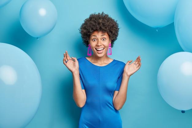 Half length shot of cheerful afro american lady enjoys festive occasion wears fashionable dress keeps palms raised