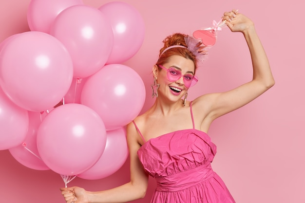 Half length shot of cheerful european woman has upbeat mood dances carefree with balloons and sweet candy poses against rosy background being on party.