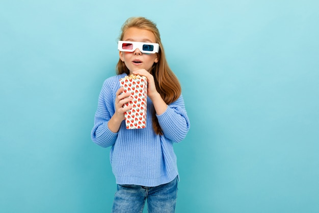 Half-length shot of a cheerful stylish girl on a blue background with glasses for a 3d movie and a bucket of popcorn