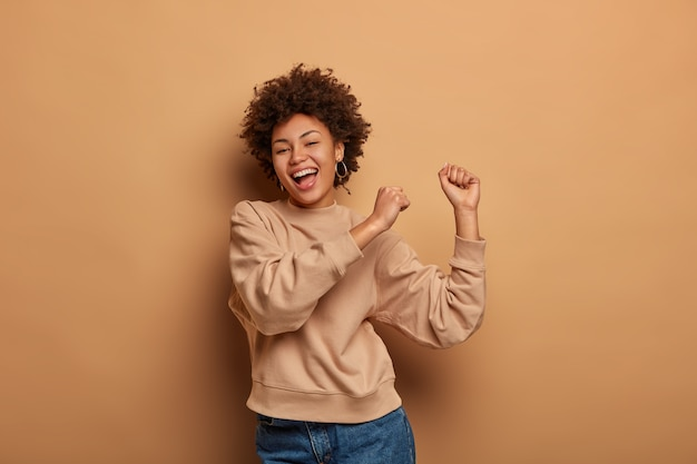 Half length shot of dark skinned girl does victory dance, laughs happily, celebrates victory, raises hands up, moves with rhythm of loud music, feels like champion, dressed in casual clothes