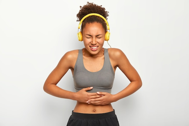 Half length shot of dissatisfied woman with curly hair, listens music with headphones, suffers from painful cramps in belly, isolated over white background