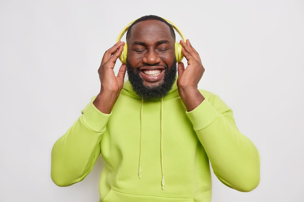 Half length shot of handsome cheerful bearded guy with dark skin listens to music in wireless headphones smiles toothily has perfect white teeth wears green sweatshirt isolated over white wall