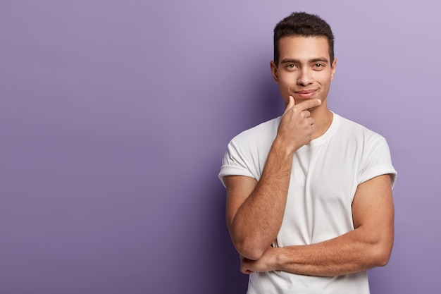 Half length shot of handsome european man holds chin, looks with satisfied confident expression directly, wears white t shirt, poses in  over purple wall, free space left aside