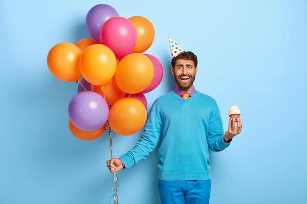Half length shot of handsome guy with birthday hat and balloons posing in blue sweater