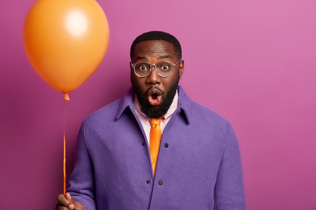 Half length shot of impressed bearded man keeps mouth opened, wears transparent glasses, holds inflated balloon