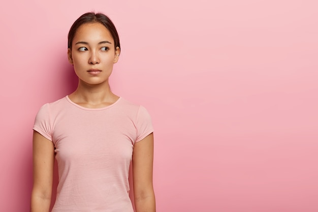 Half length shot of lovely serious woman looks aside on blank space, has pensive expression, healthy skin and specific appearance, wears casual t shirt, isolated on pink wall. ethnicity concept