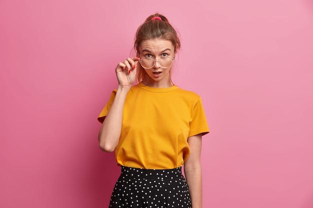 眼鏡を通して不思議に思う驚いた女性のルックスのハーフレングスショット