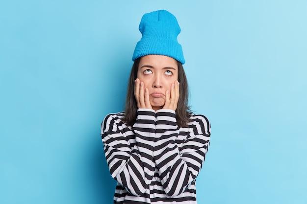 Половинный снимок скучающей подчеркнутой и невеселой девушки-подростка, сосредоточившей ладони на щеках, сосредоточенных выше, с недовольным неохотным выражением лица позирует на синей стене, одетая в повседневную одежду