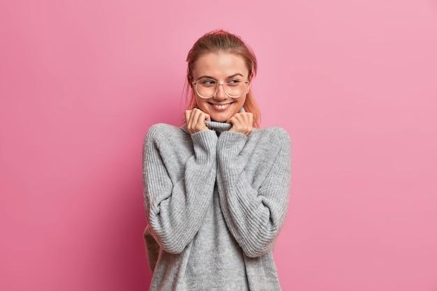 特大の灰色のセーターを着た魅力的な美しい大人の女性のハーフレングスショットは優しく微笑んで、何か楽しいものを思い出し、光学眼鏡をかけています