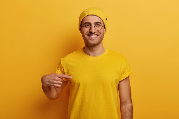 Половинный снимок веселого мужчины указывает на желтую футболку, с радостным выражением лица рекламирует новый наряд, позирует на ярком фоне