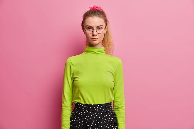 学校の準備ができている自信のある真面目な女子高生の半分の長さのショット、直接見て、ポニーテールを持ち、緑のタートルネックとスカートを着ています