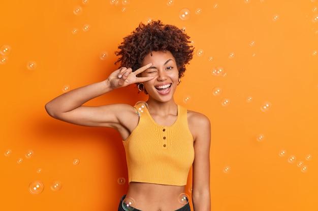 좋은 신체적 모양의 곱슬 머리 아프리카 계 미국인 여성의 절반 길이 샷은 자른 상단을 착용하여 주황색 벽 위에 광범위하게 고립 된 눈 미소를 통해 평화 제스처를 만듭니다.