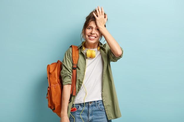 不機嫌な女性の半分の長さのショットは額に手を保ち、何かを後悔し、不満に見え、首にヘッドフォンを持っています