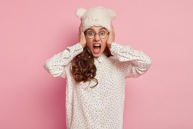 Половина кадра эмоционально раздраженной симпатичной женщины, которая громко кричит, закрывает уши, выражает отрицательные эмоции, носит теплую белую шляпу