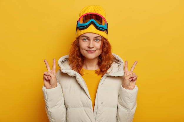 生姜のきれいな女性の半分の長さのショットは、腕を上げ、平和または勝利のジェスチャーを行い、黄色の背景の上に分離された冬の白衣を着たスキーゴーグルを使用しています。