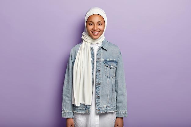 Снимок половинной длины радостной арабской женщины в белом хиджабе и джинсовой куртке