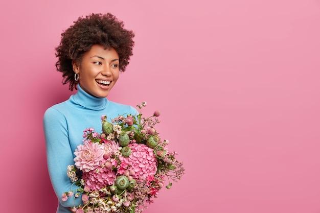 좋은 매력적인 아프리카 미국 여자의 절반 길이 샷은 신선한 꽃의 무리를 보유