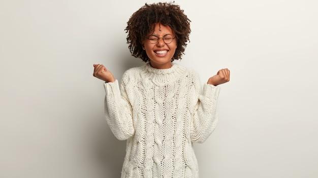 Половина кадра оптимистичной женщины, которая чувствует себя победительницей, поднимает руки в кулаки, одетая в белый вязаный свитер, закрывает глаза от удовольствия, изолированного над белой стеной. люди, успех, концепция радости