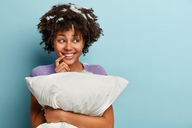 Половинный снимок позитивной темнокожей девушки с мечтательным выражением лица, держит руку у рта, искренне улыбается, видит приятный сон ночью, держит подушку, готовится ко сну, изолировано на синем