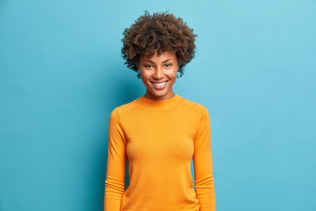青い壁に分離されたカジュアルなオレンジ色のジャンパーに身を包んだ素敵な晴れやかな笑顔の喜ばしい表情でかなり陽気な若い女性の半分の長さのショット