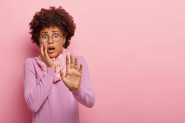 怖がっているアフリカ系アメリカ人女性の半分の長さのショットは、手のひらを伸ばしたままにし、恐れを持って見つめ、何かひどいことを恐れています