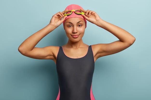 Опытный профессиональный пловец поправляет очки, носит купальник и шапочку для плавания.