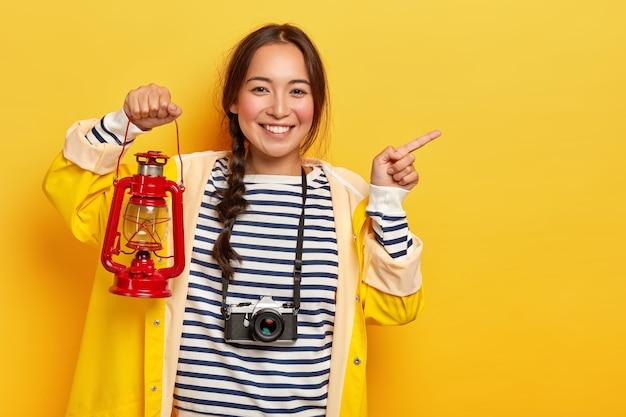 웃는 한국 여성 관광객의 절반 길이 샷은 검지로 멀리 가리키고, 가스 램프를 들고, 목에 레트로 카메라를 착용하고, 캐주얼 한 옷을 입고, 유쾌하게 미소를 짓고, 노란색 배경 위에 절연