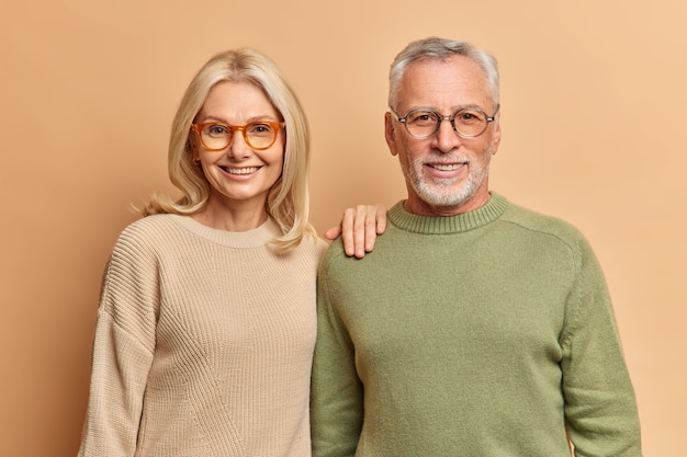 Half length shot of pleased middle aged woman and man smile pleasantly wear jumpers and spectacles