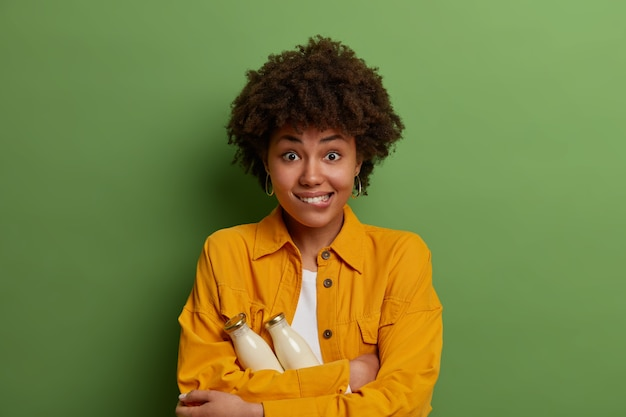 Half length shot of positive afro american woman bites lips, holds two glass bottles of plant based milk, drinks only organic beverage, keeps to healthy diet, wears yellow shirt, stands indoor