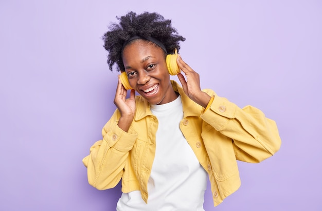 Half length shot of pretty positive millennial girl with dark skin curly hair listens favorite music via headphones dressed in yellow jacket smiles gladfully isolated on purple