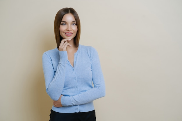Half length shot of pretty slim woman dressed in casual blue jumper, keeps hand under chin