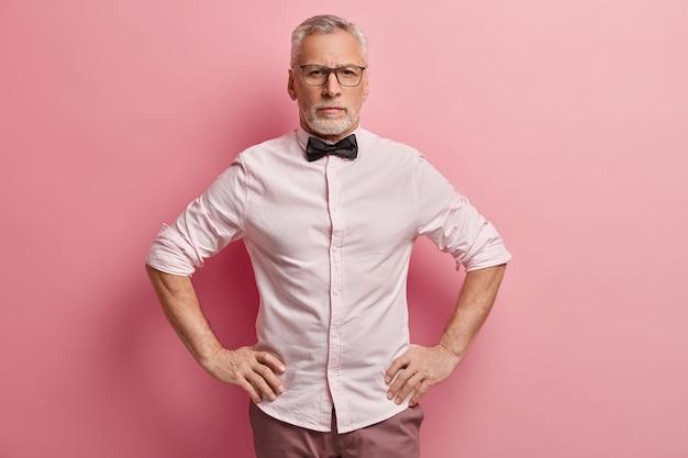 Mezza lunghezza ripresa di imprenditore maschio maturo sicuro di sé tiene entrambe le mani sulla vita, guarda seriamente la telecamera, pronto per il lavoro, indossa abiti formali, occhiali ottici per la correzione della vista
