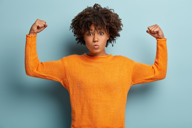 Half length shot of serious afro american woman with curly hair, raises hands, shows muscles, tries to be strong