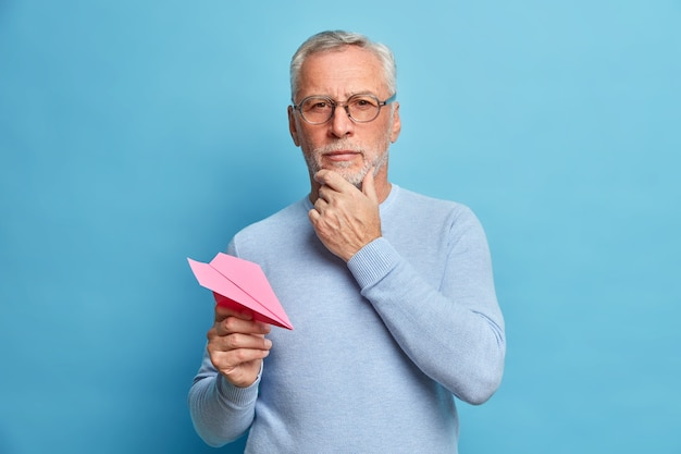Half length shot of serious bearded man pensioner holds chin and looks directly at front holds pink handmade aircraft dressed casually has ambitious self confident expression stands indoor