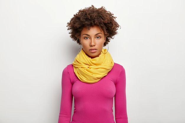 Half length shot of serious dark skinned curly haired woman wears big round earrings, yellow scarf and rosy turtleneck, looks directly at camera, poses against white background.