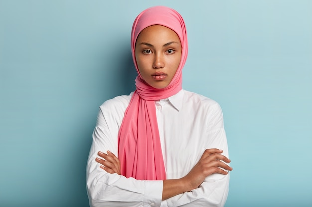 Half length shot of serious self assured woman wears traditional pink hijab, keeps arms crossed, dressed in white shirt, stands against blue wall, listens interlocutor with interest. religion