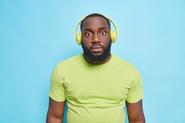 Half length shot of surprised man with thick beard reacts on something amazing dressed in casual t shirt listens music via headphoneshears shocking news isolated over blue wall