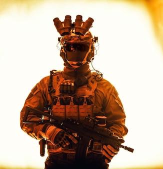반테러 분대원, 특수 작전 군인, 야간 투시 장치가 있는 전술 탄약을 사용하는 군사 회사 용병, 무장된 짧은 배럴 돌격 소총의 절반 길이 스튜디오 초상화