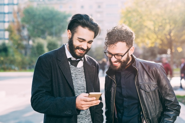 Half length of two young bearded modern businessman using smart phone