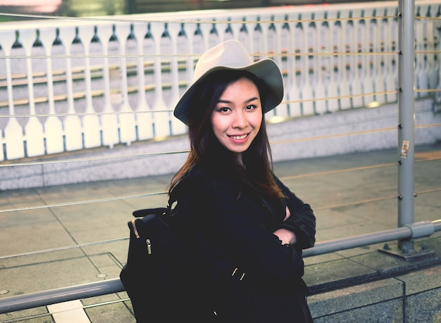Half length of young beautiful asiatic hipster woman in the city smiling looking in camera.