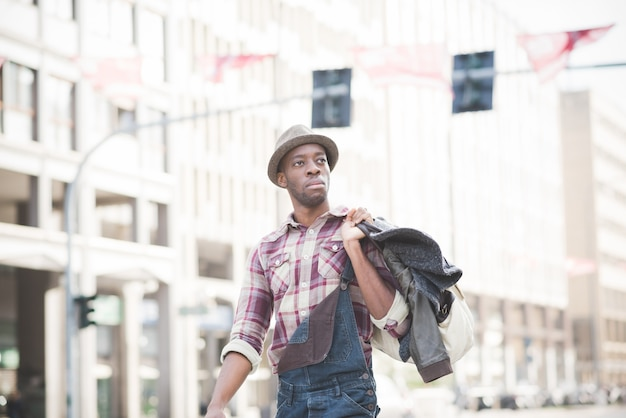 Half length of young handsome afro black man walking in the street of the city