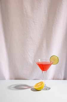 Half lime with cocktail drink garnish with cocktail on desk against isolated on white background